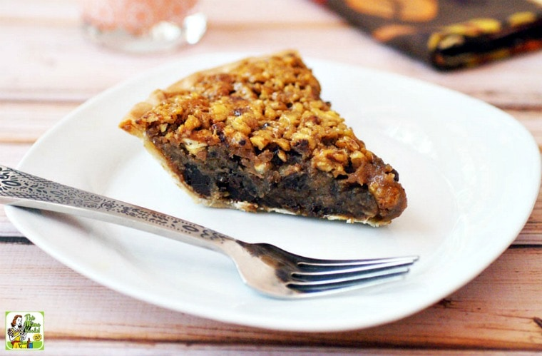 A slice of Chocolate Pecan Pie on a white plate with a silver fork.