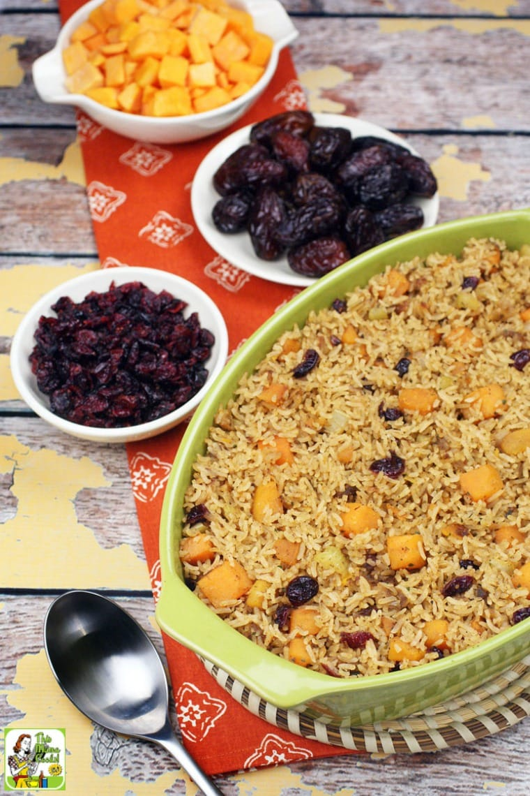 A casserole dish of rice stuffing with bowls of cranberries, squash and dates