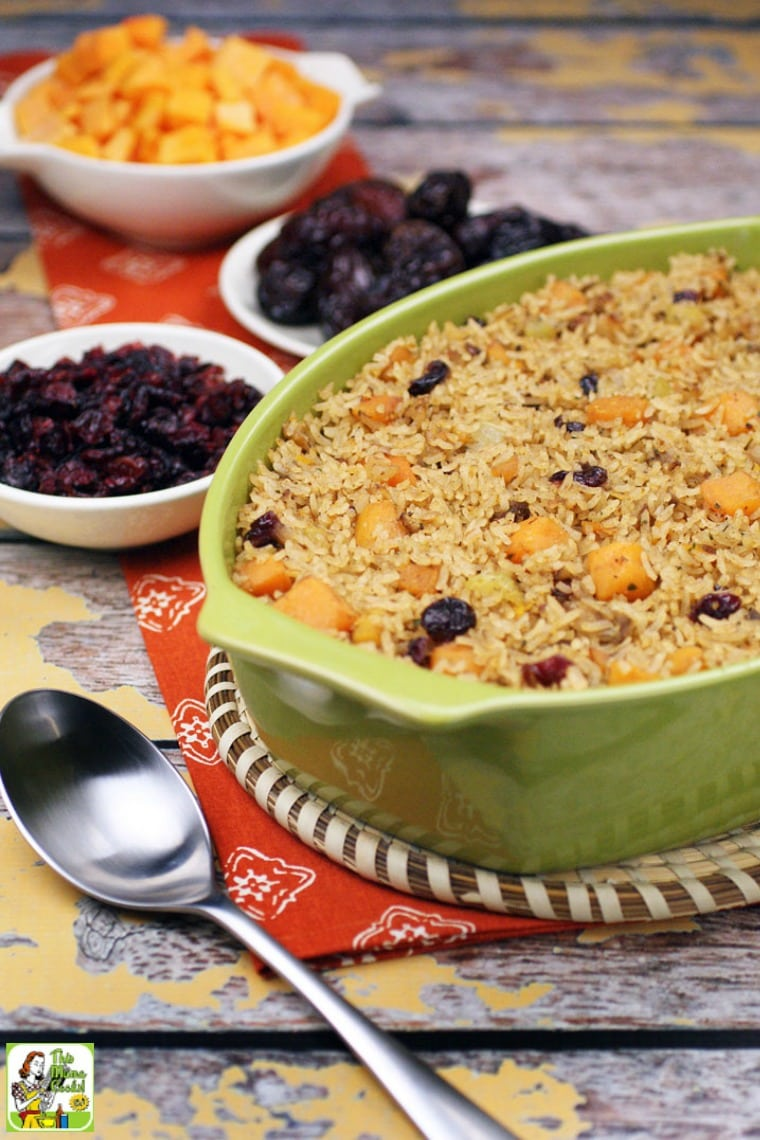 A casserole dish of rice stuffing with bowls of cranberries, squash and dates and a silver serving spoon