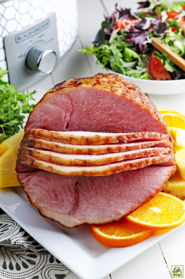 Slow cooker sliced ham on a plate with a bowl of lettuce and a crock pot in the background.