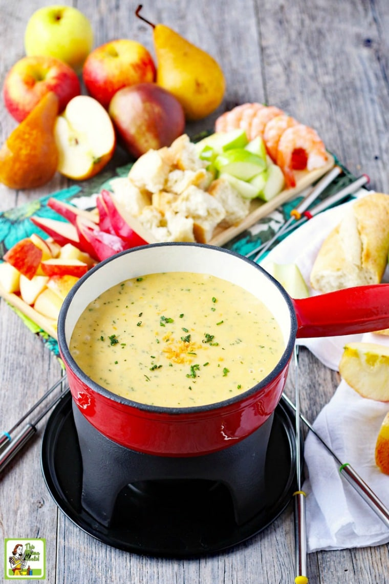 A pot of brie fondue and fondue forks with dipping foods on trays in the background