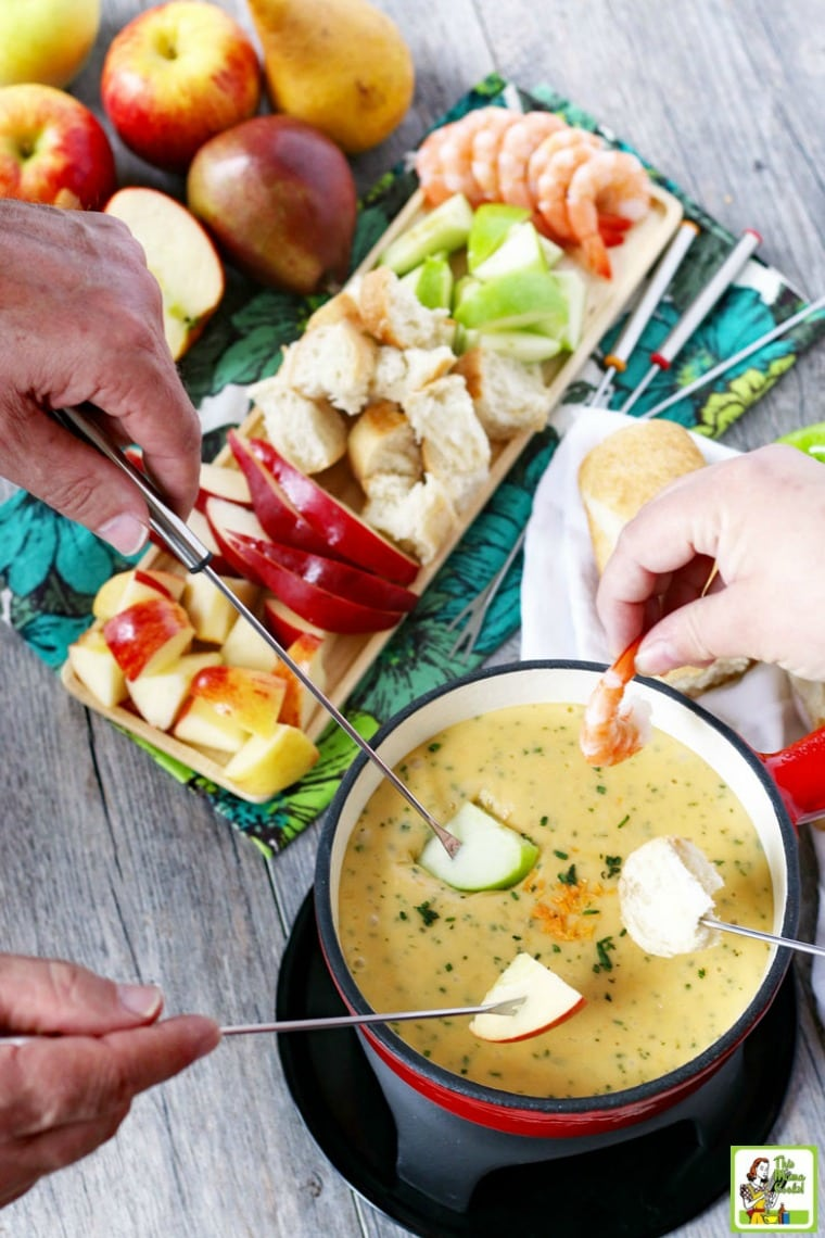 Hands dipping fruit into brie cheese fondue recipe in red pot. Fruit, bread, shrimp and other fondue dippers on tray.