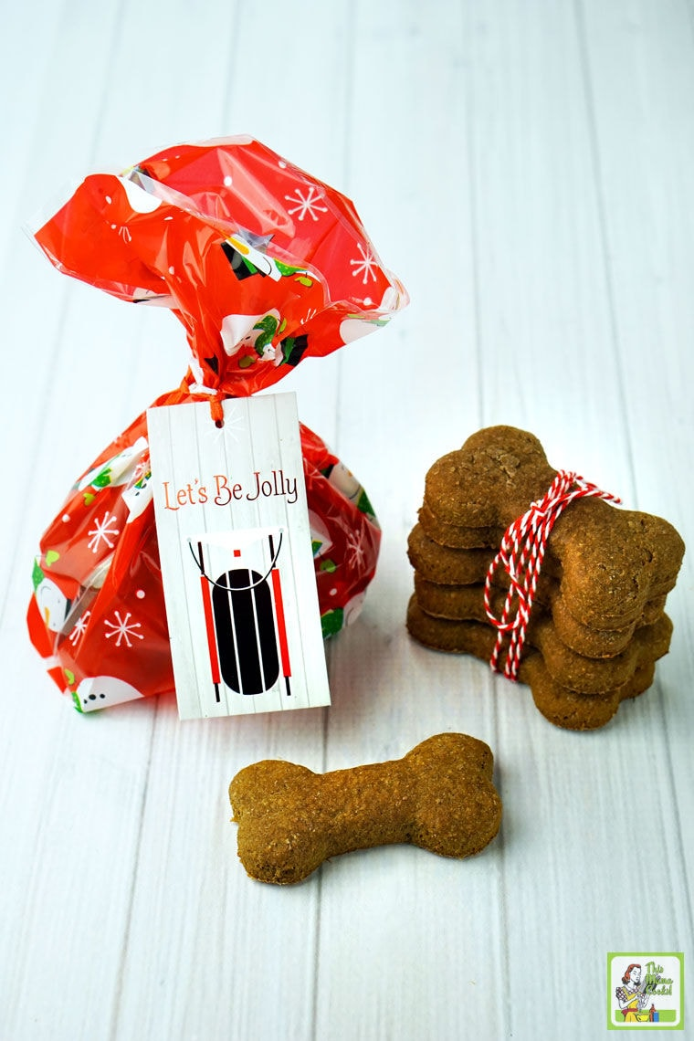 Dog bone shaped biscuits wrapped in red string and wrapped up in a festive bag with a gift tag.