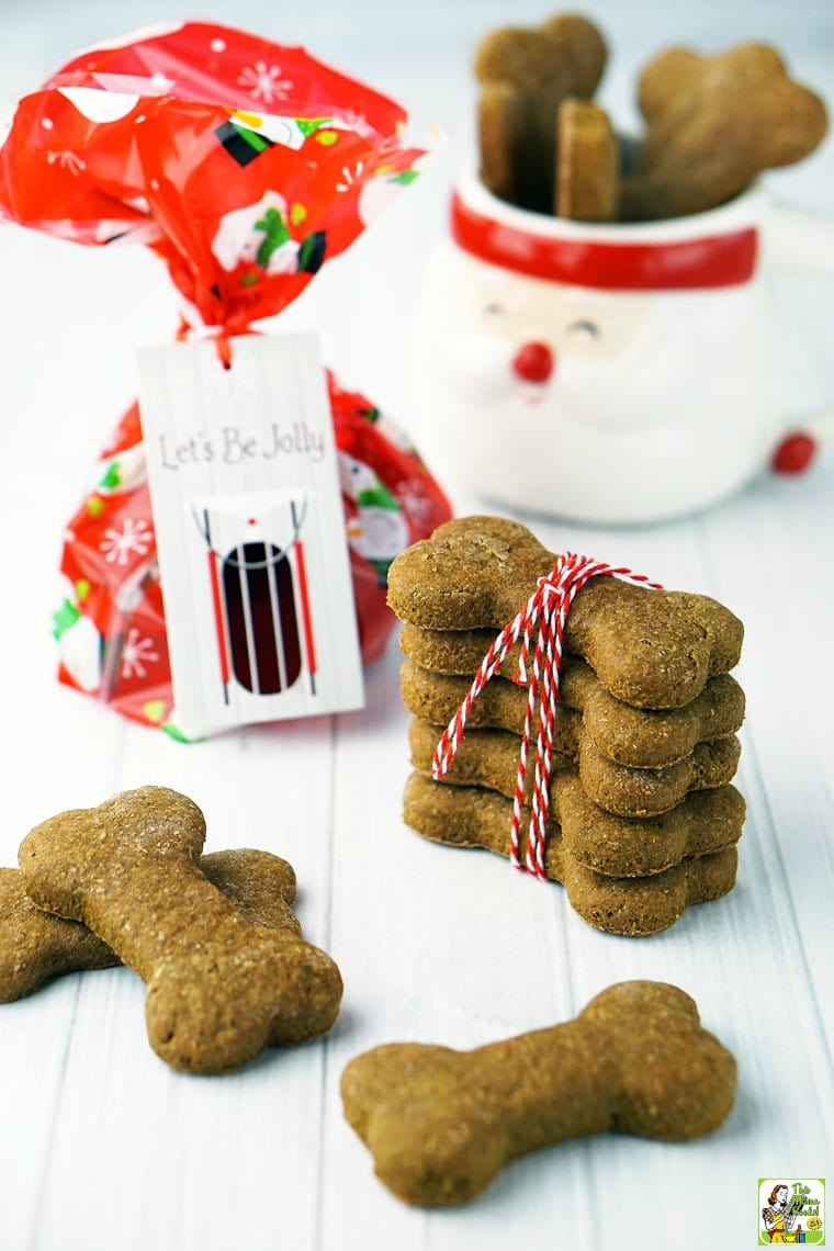 Homemade dog biscuits and treats in a Santa mug, wrapped in string, and in a gift bag.