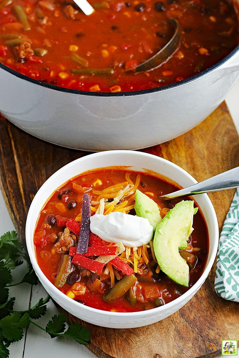 Overhead shot of a cooking pot and bowl of taco soup with spoons on a wooden cutting board with a napkin and bunch of cilantro.