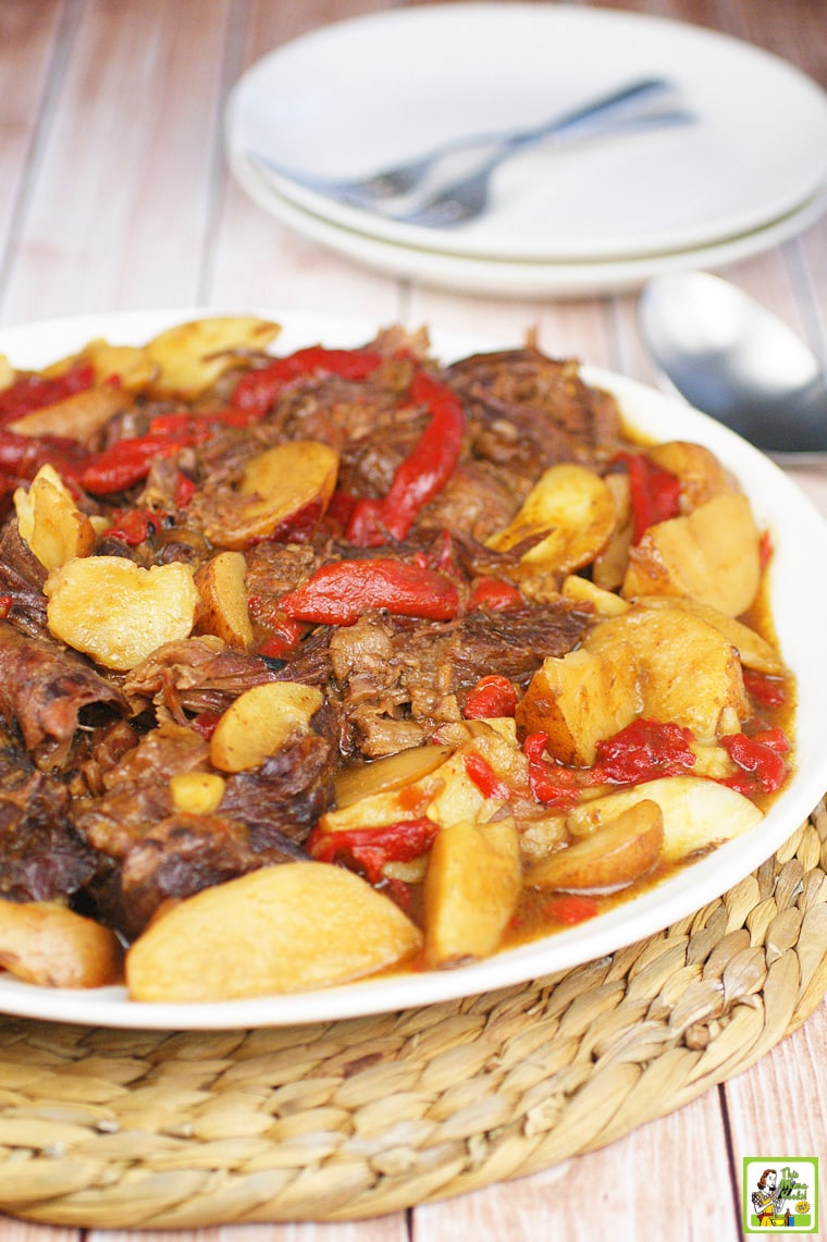 A plate of pot roast with red peppers and potato wedges on a straw mat with plates and forks in the background.