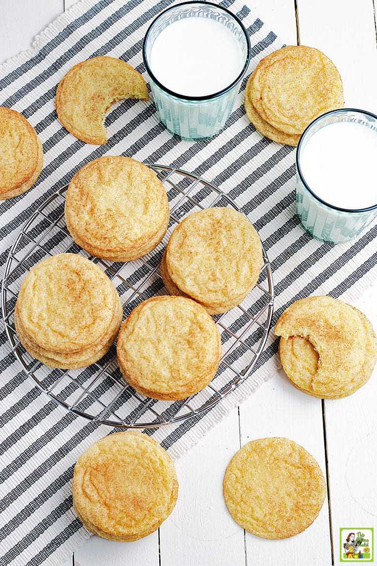 Overhead shot of rice flour snickerdoodles cookies on a striped napkin and wire rack with glasses of milk.