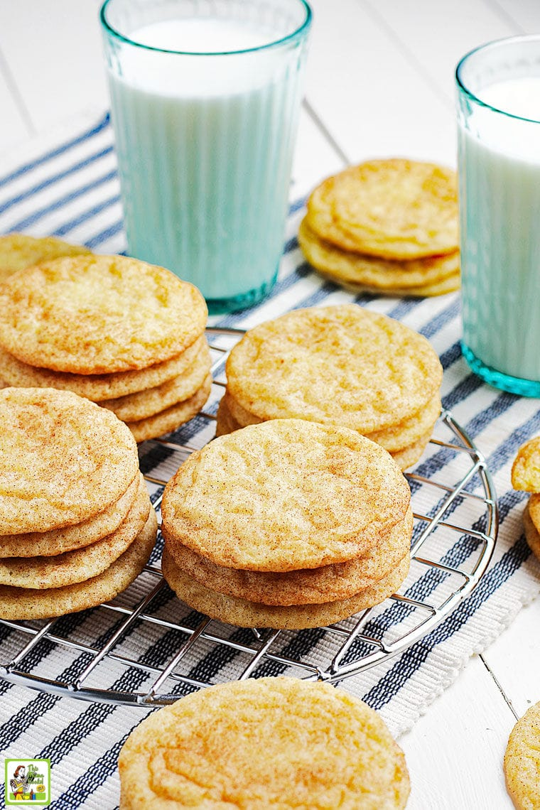Gluten free snickerdoodles cookies on a wire rack on a striped napkin with glasses of milk.