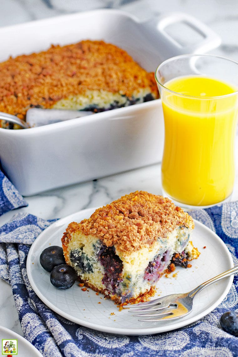 A piece of blueberry muffin coffee cake on a white plate with fork, a baking dish of coffee cake, and a glass of orange juice on a blue and white napkin.