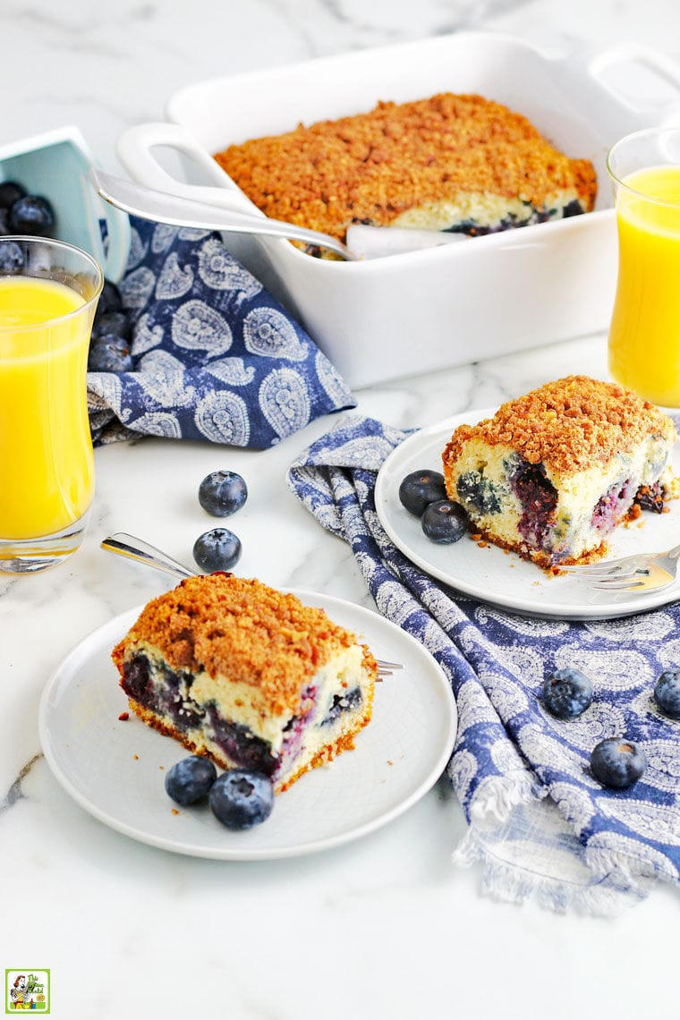 Pieces of blueberry muffin cake on white plates with fork, a baking dish of coffee cake, and glasses of orange juice on a blue and white napkins.
