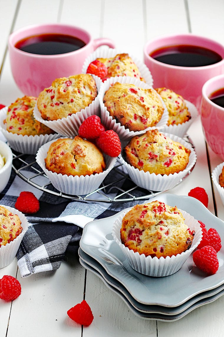 A tabletop with raspberry muffins in white cupcake liners on white plates and on black and white napkins with red raspberries and pink mugs of black coffee.