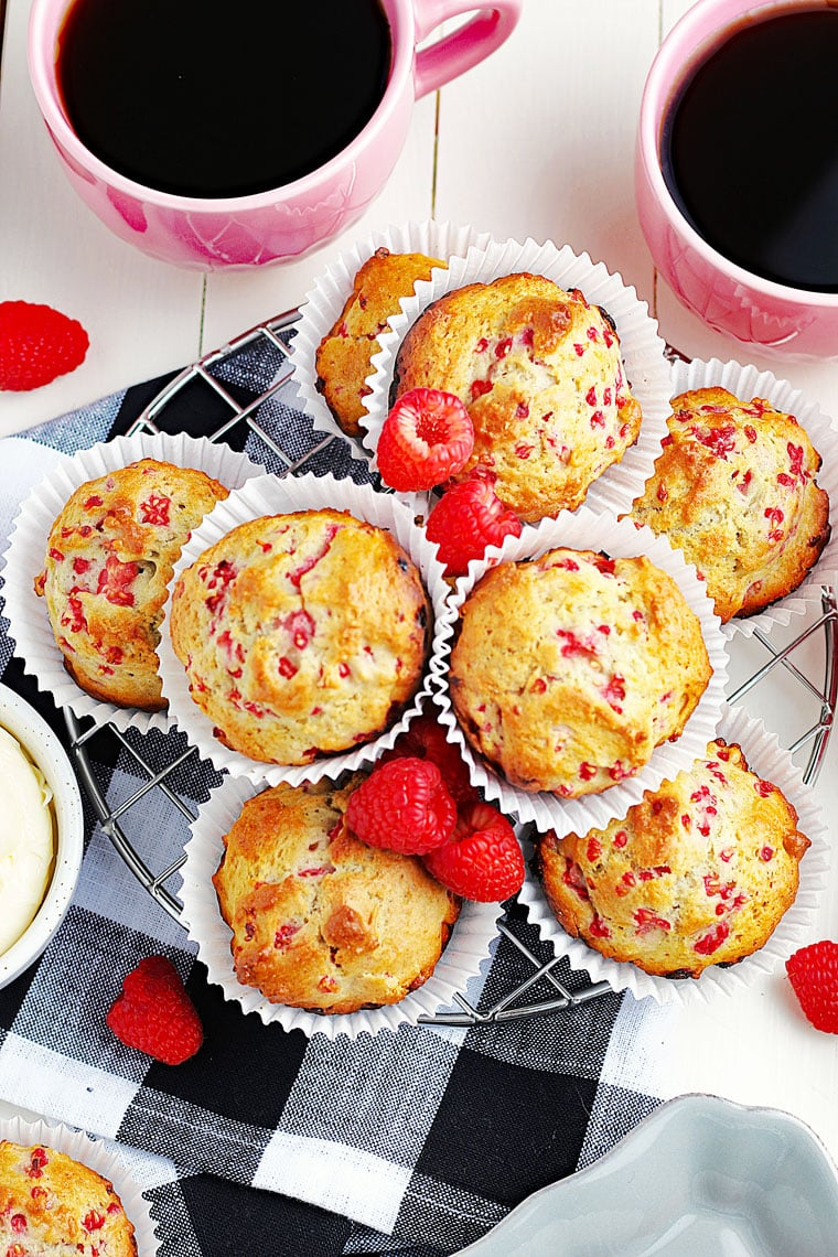 Overhead shote of a bunch of raspberry yogurt muffins in white paper liners with fresh liners on a wire rack on a black and white napkin with pink mugs of black coffee.