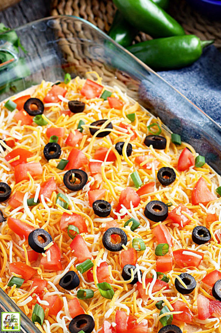 A casserole dish of layered taco dip with cheese, olives, tomatoes, and green onions.