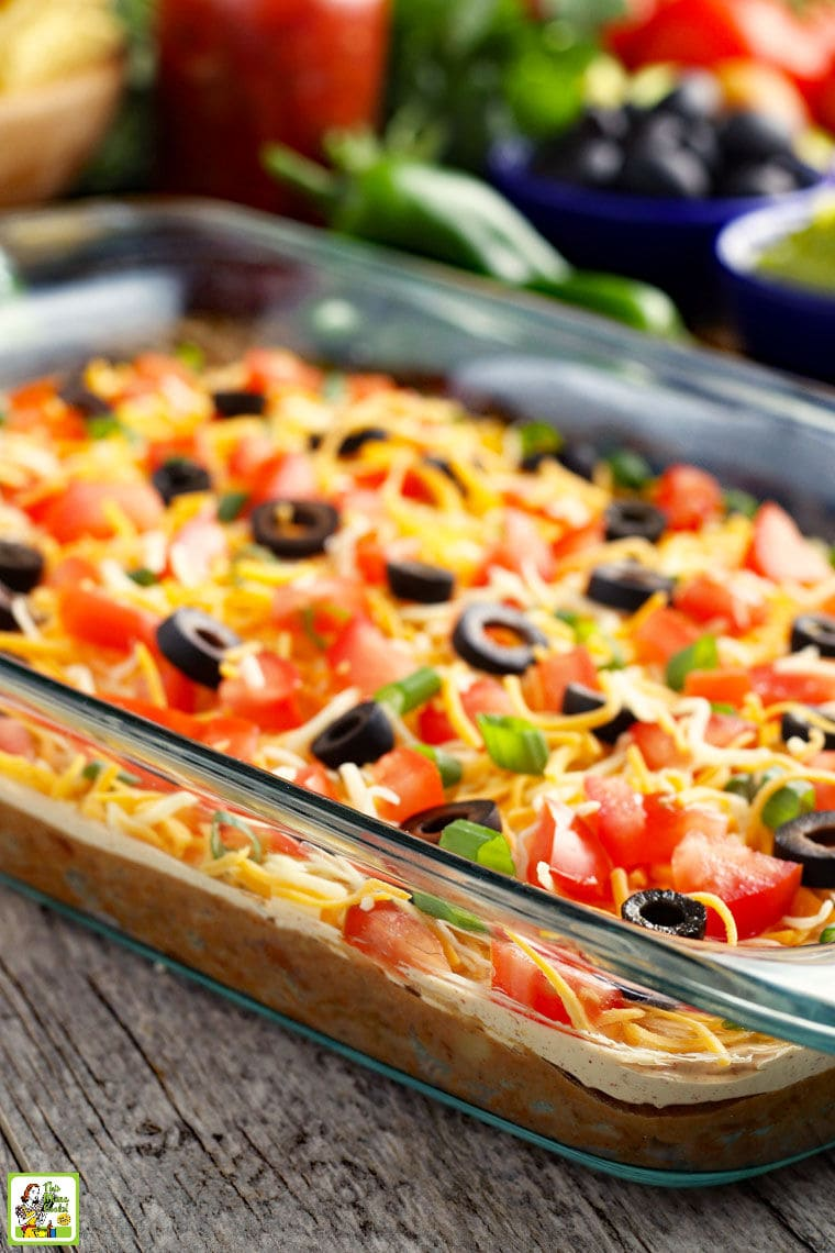 A glass casserole dish of taco dip with layers of cheese, olives, tomatoes, green onions, sour cream, refried beans, and ground beef.