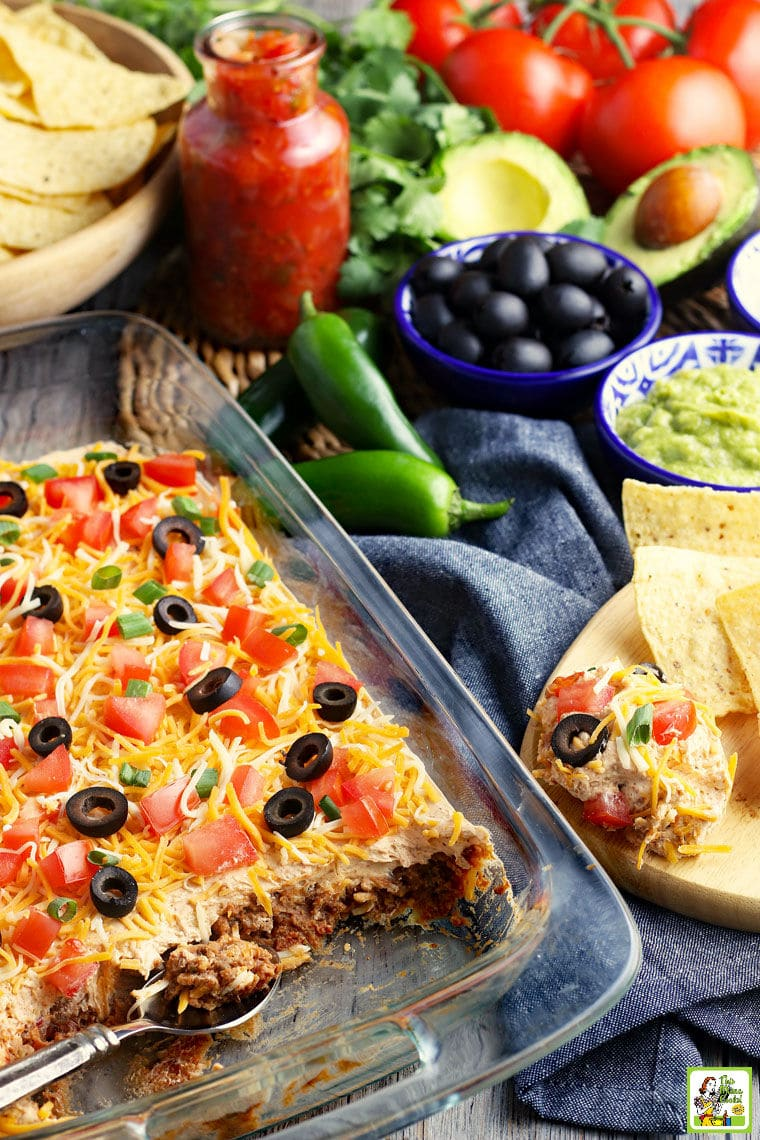A glass casserole dish of taco dip with layers of cheese, olives, tomatoes, green onions, sour cream, refried beans, and ground beef. With olivers, avocadoes, tortilla chips, chiles, and tomatoes in the background.