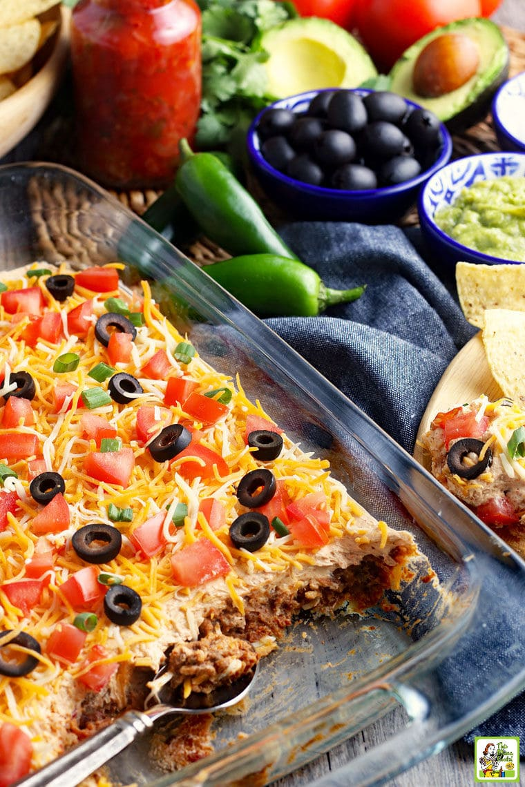 A casserole dish of taco dip with cheese, olives, tomatoes, and green onions with layers of ground meat and refried beans.