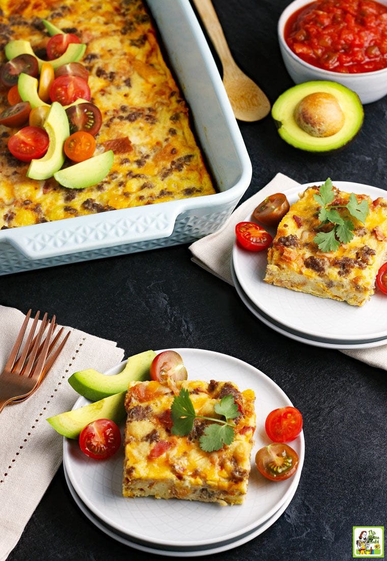 Plates of Overnight Breakfast Casserole with avocados and tomatoes.