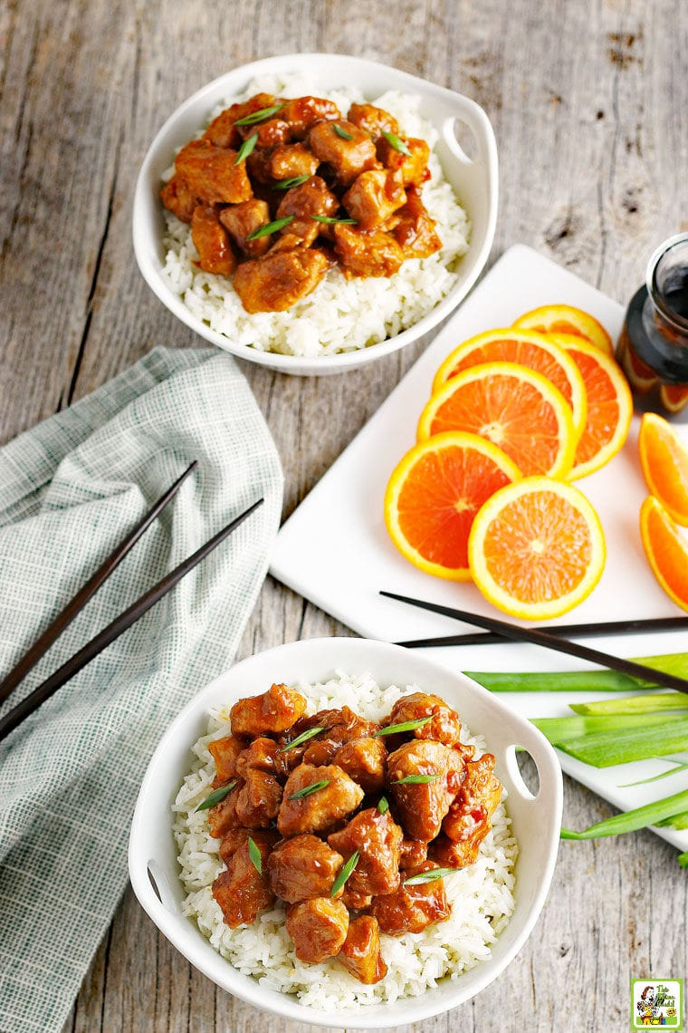 Two bowls of Orange Chicken on white rice with slices of oranges, soy sauce, green onions, and chopsticks.
