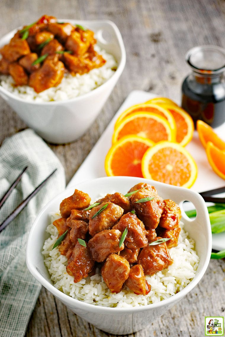 A bowl of Orange Chicken on white rice with slices of oranges, soy sauce, green onions, and chopsticks.