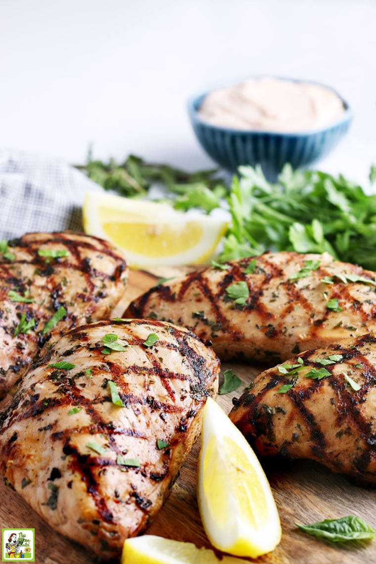 Grilled pieces of Easy Marinated Chicken on a wooden cutting board, with lemon wedges, parsley, and a bowl of dipping sauce.