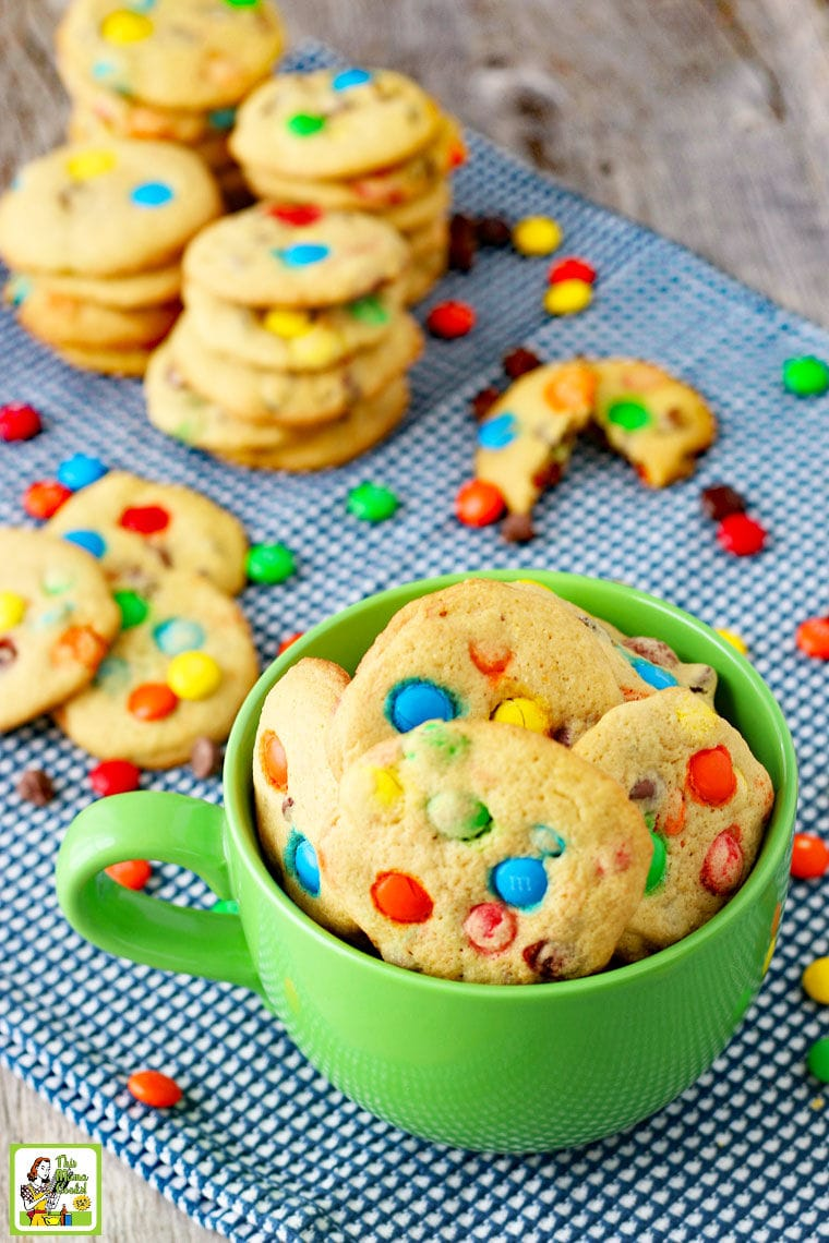 M&M Chocolate Chip Cookies in a green mug with stacks of M&M cookies in the background