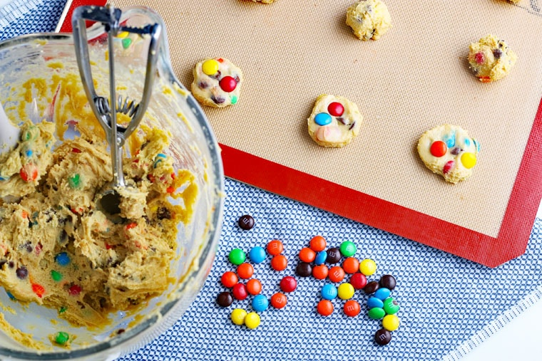A bowl of M&M Chocolate Chip Cookies dough and a baking sheet of dough balls ready to be baked.