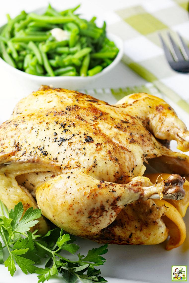 Roasted whole chicken with a bowl of green beans on a green and white checkered tea towel