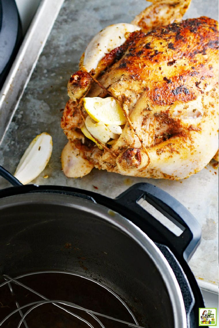 Cooked roasted chicken on a baking sheet next to a pressure cooker