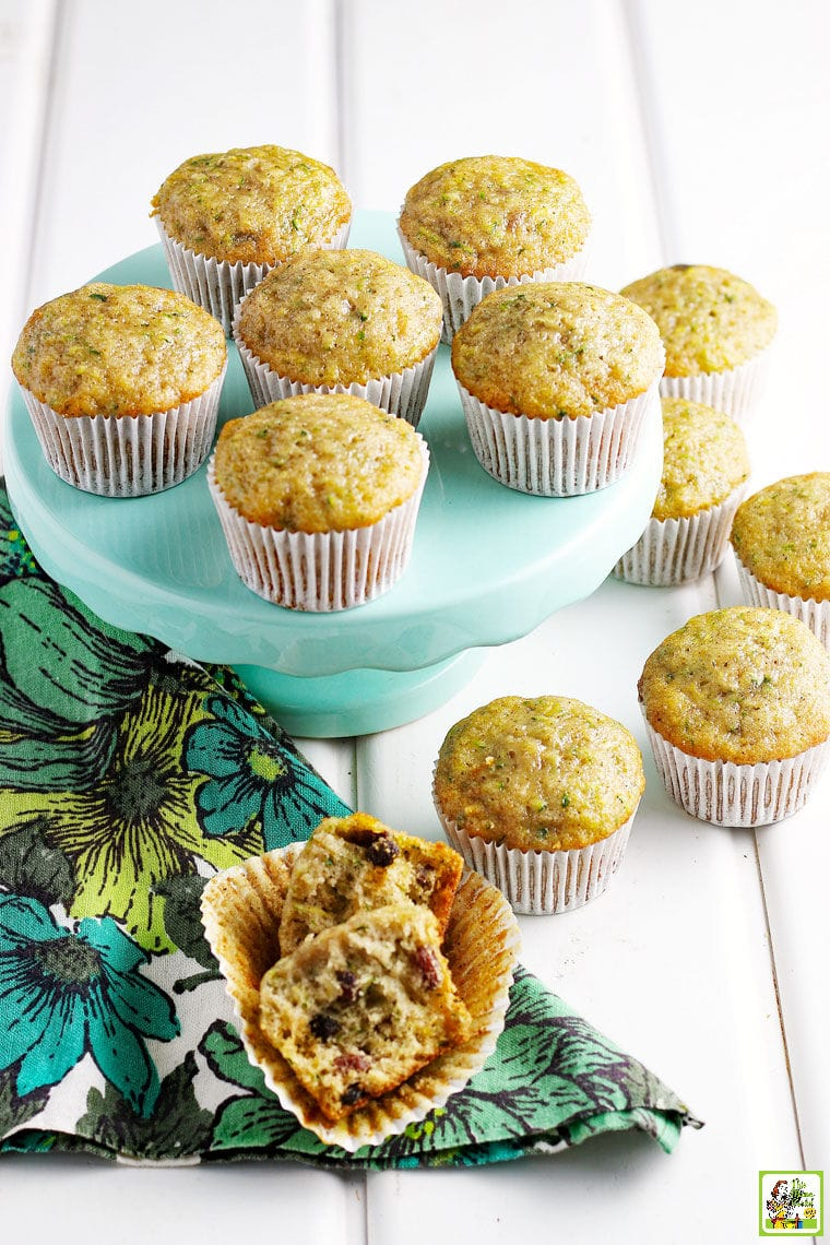 Zucchini Muffins on a cake stand with a colorful floral napkin