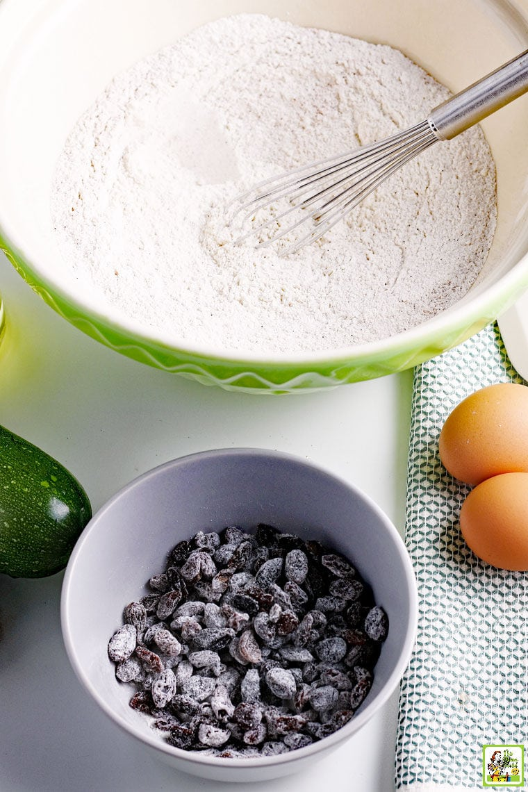 Ingredients for making zucchini muffins in a bowl with whisk