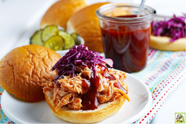 BBQ Chicken sandwich on a white plate with pickles with a jar of homemade BBQ, buns, purple cabbage in the background.