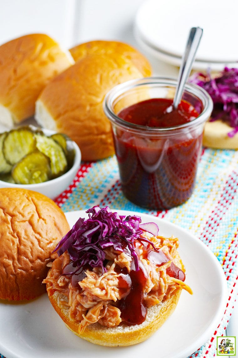 BBQ chicken sandwiches with red cabbage, pickles, BBQ sauce, and buns on a striped cloth