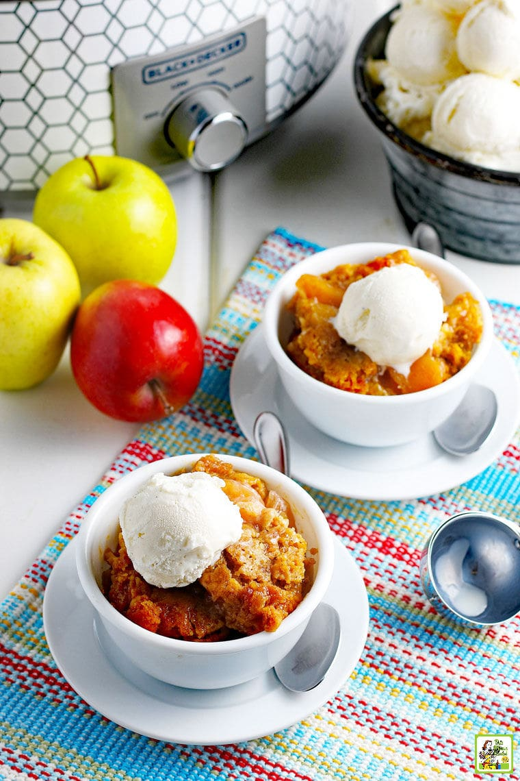 Apples, bowls of cobbler with ice cream, an ice cream scoop, on a brightly colored placemat with a slow cooker in the background.