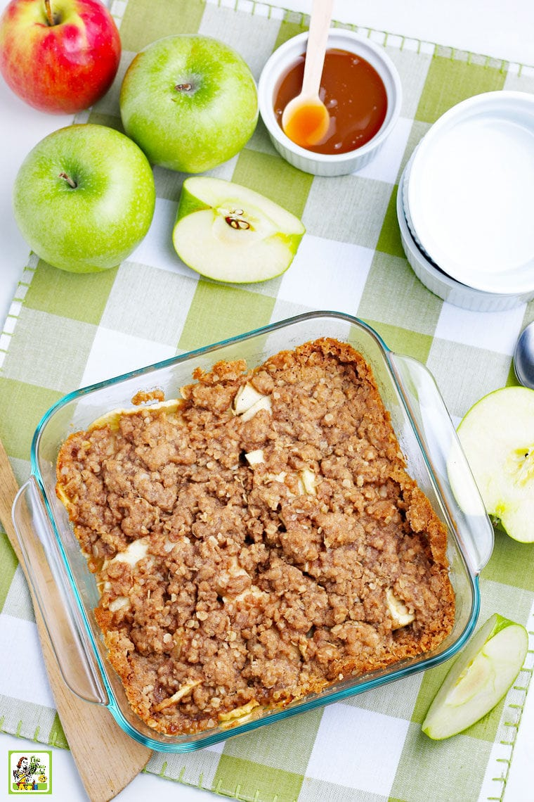 A dish of Apple Crisp with bowls, spoons and apples.