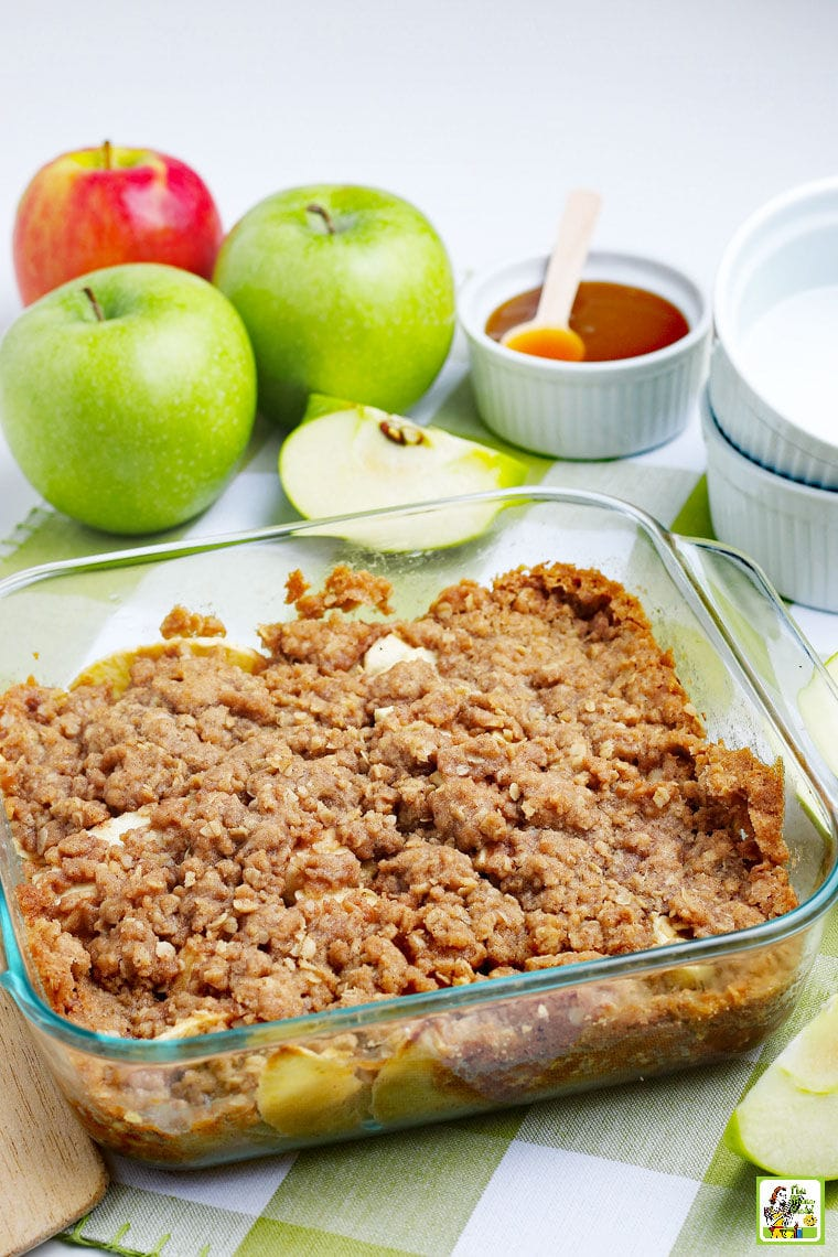 A platter of warm apple crisp with apples, apple slices, a bowl of caramel sauce, and white bowls on a green and white napkin.