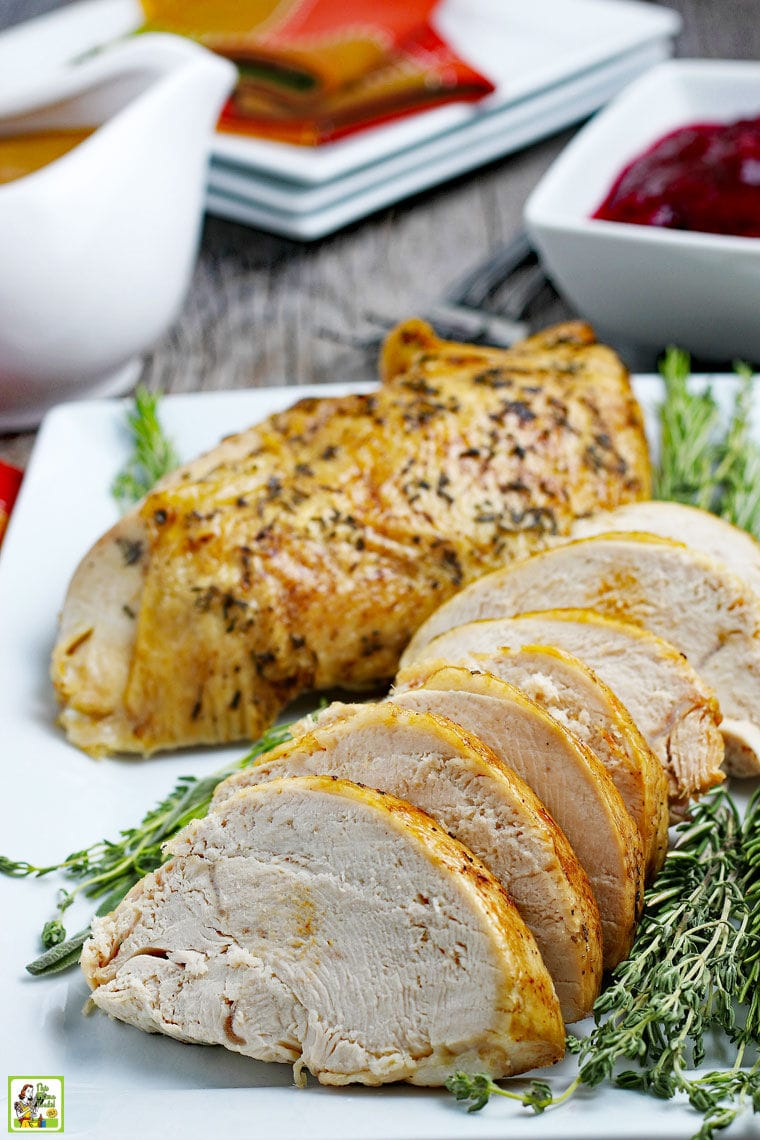 Cooked and sliced roasted turkey breast on a white platter with herbs with gravy, cranberry sauce, plates, and napkins.