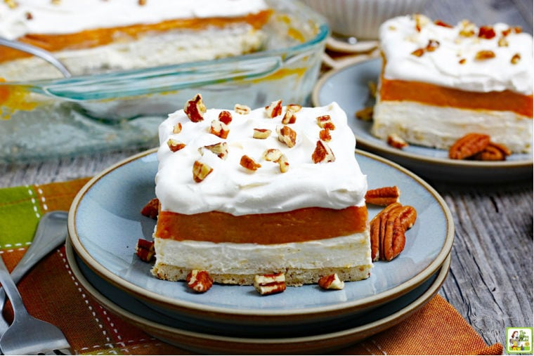 Blue plates of Pumpkin Cheesecake Lasagna with pecans on a multicolored placemat with forks with a baking dish in the background.