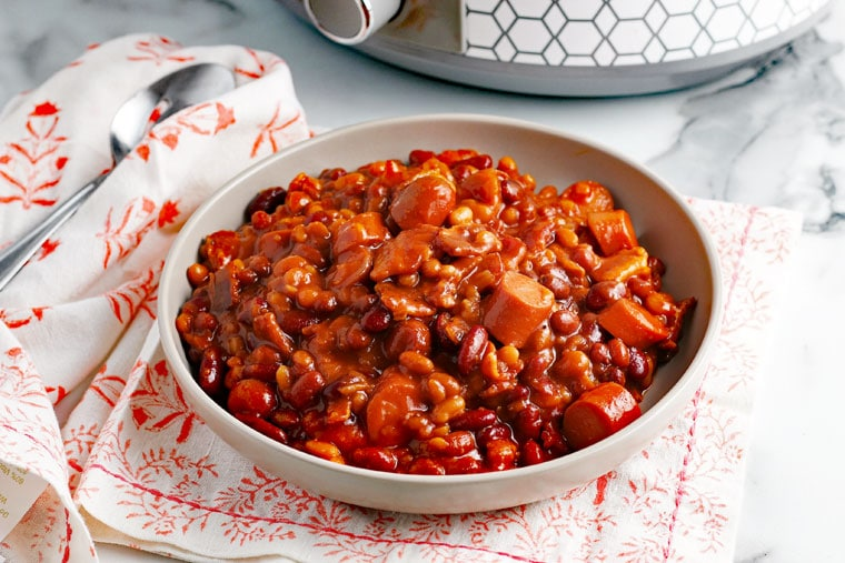 A bowl of Crock-Pot Baked Beans on a napkin with a spoon with a slow cooker in the background.