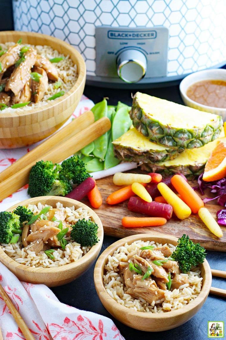 A slow cooker, serving bowls of teriyaki chicken on rice with broccoli, wooden serving utensils, wooden cutting board, fruits and vegetables, on colorful napkins.