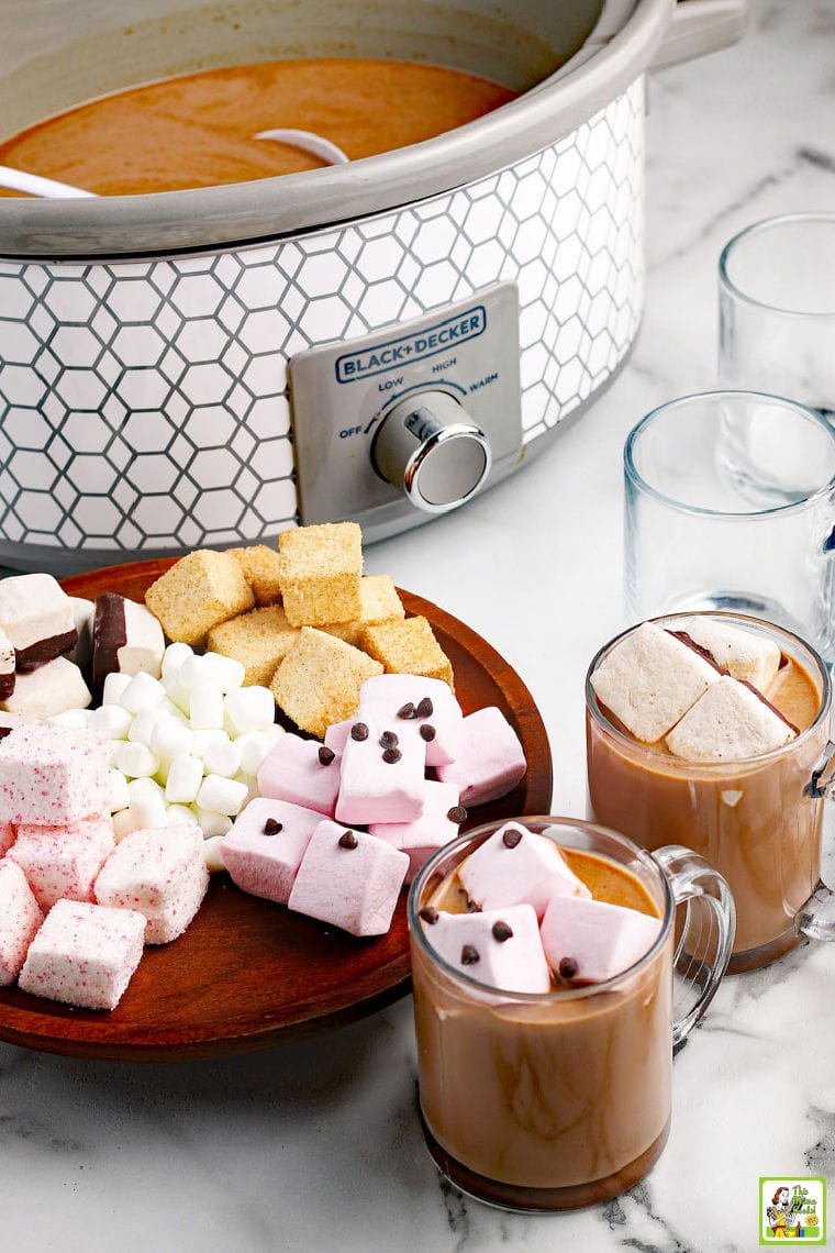 Slow cooker hot chocolate served in glass mugs with colorful marshmallows and chocolate chips.