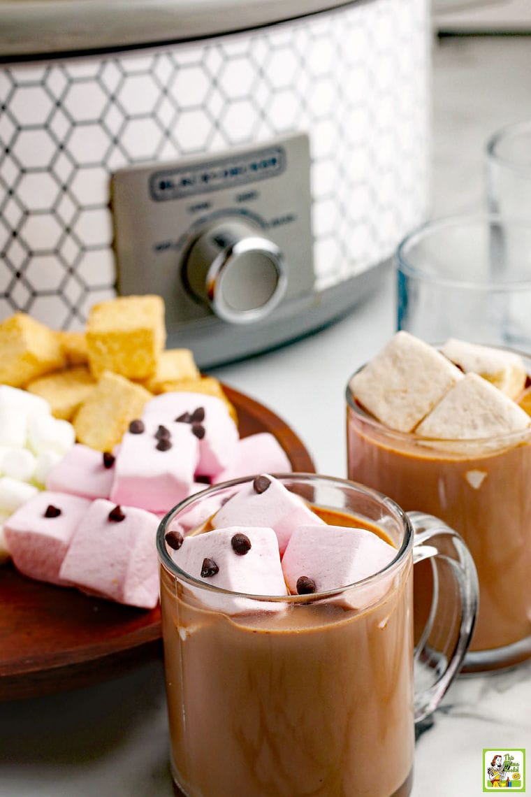 Mugs of hot chocolate with marshmallows in glass mugs with a slow cooker in the background.