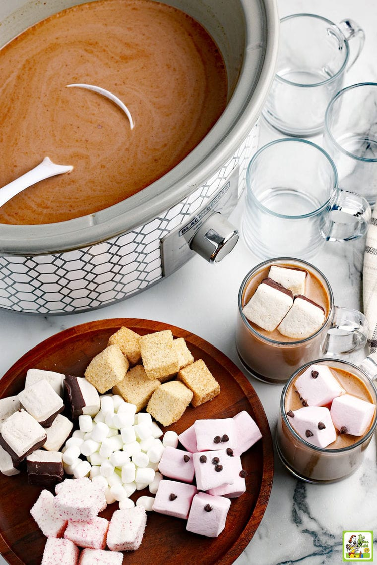 Overhead shot of a crock pot of hot chocolate with a ladel, a wooden cutting board covered in colorful marshmallows, and glass mugs of hot chocolate and empty mugs on a marble countertop.