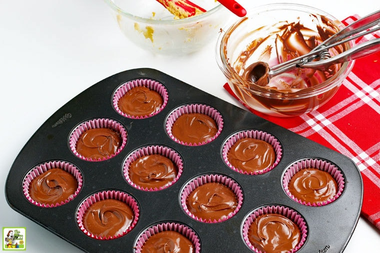 Adding the final layer of melted chocolate to the homemade peanut butter cups with empty bowls and a cookie scoop in the background.