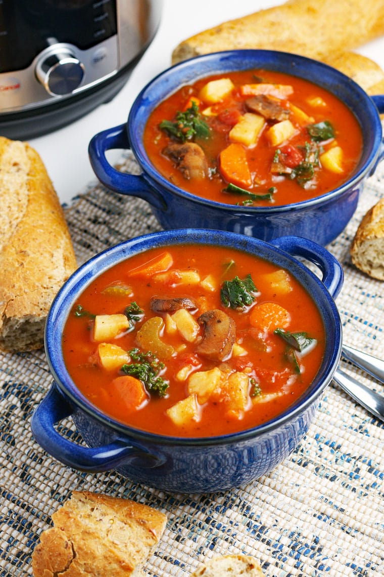 Blue bowls of vegetable soup, French bread, spoons, and a pressure cooker on a blue and white placemat.