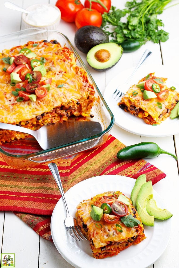 Chicken enchiladas in a casserole dish and on white plates with avocados on striped napkins.