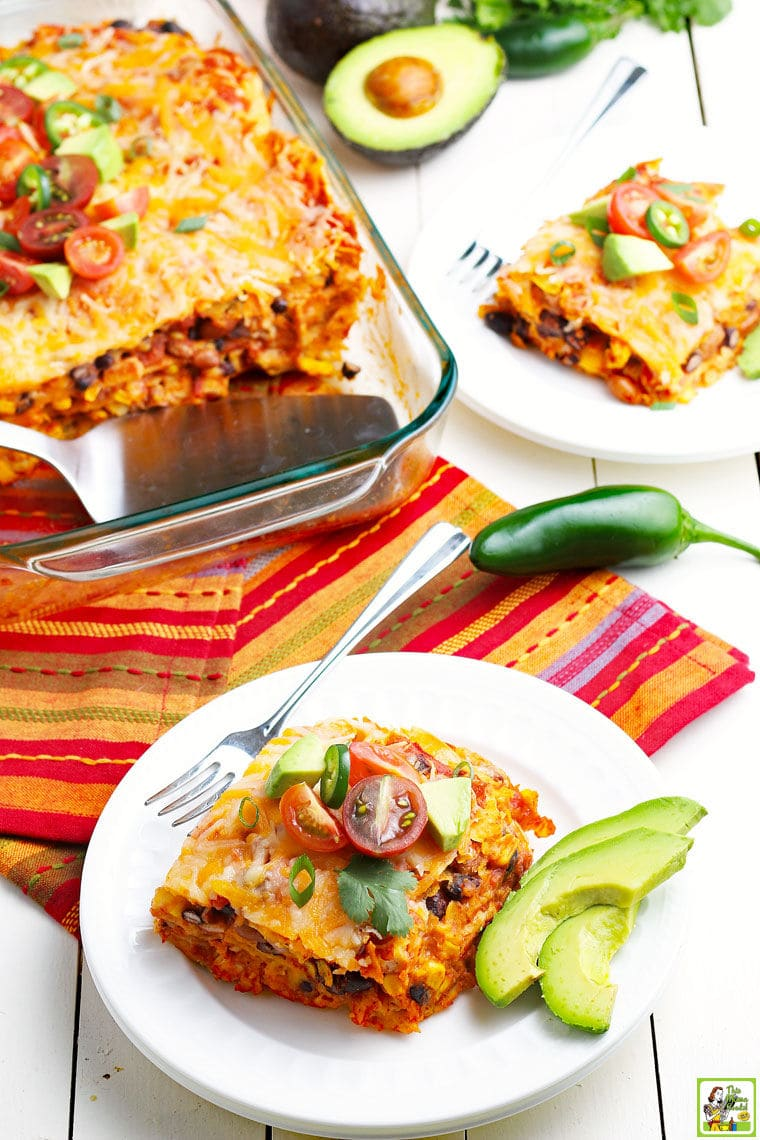 A glass casserole dish of chicken enchilada with white plates of slices of chicken enchilada with chili peppers, avocado, and tomatoes on festive napkins.