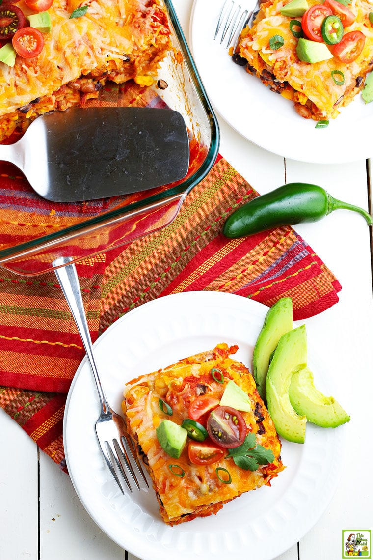 A square slice of enchilada casserole on a white plate with slices of avocados and cherry tomatoes with a glass casserole dish of enchiladas with a silver serving spoon placed on a colorful napkin.