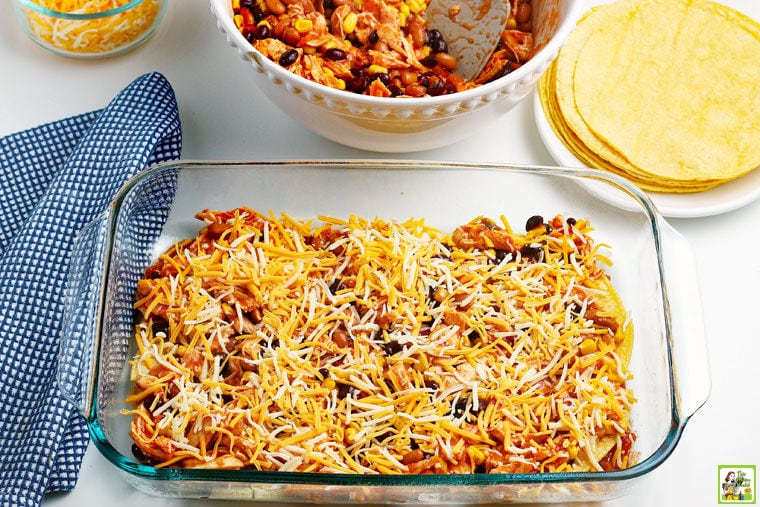 Layer of the chicken enchilada casserole with shredded cheese in a glass baking dish.