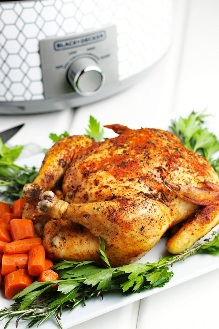 A slow cooker whole chicken on a platter with carrots and parsley.