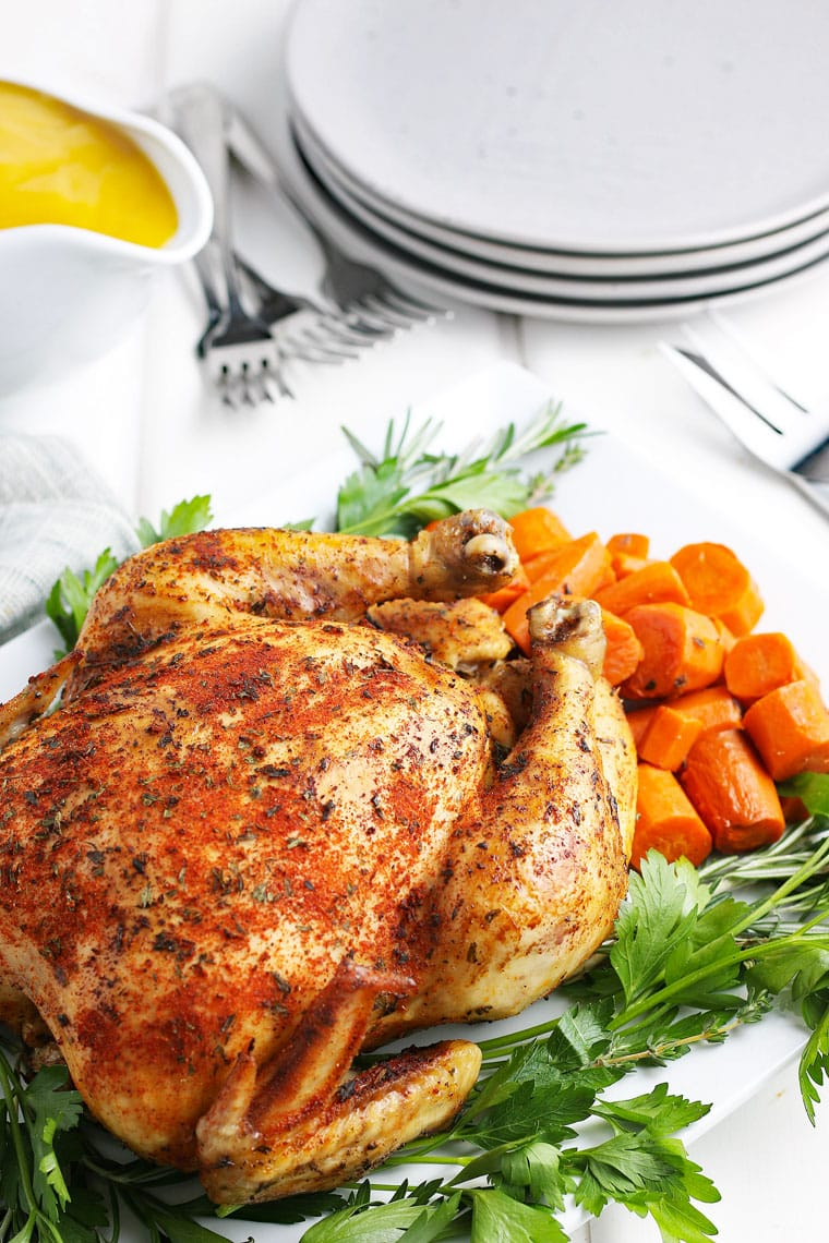 A crockpot whole chicken on a platter with carrots, gravy, plates, and forks.